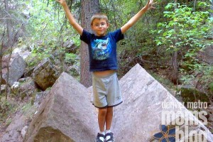 A boy, standing on a boulder with his arms up