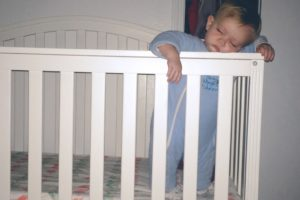 Little Lady fell asleep on the crib rail while protesting the new sleep situation.