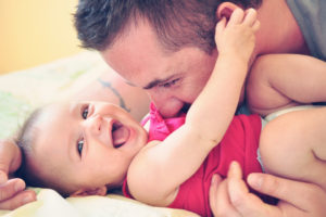 Father with smiling baby daughter dressed in red