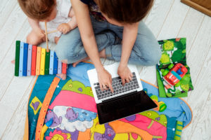 Close up photo of young mother working on laptop with her toddler child. Freelance business concept. Selective focus top view.